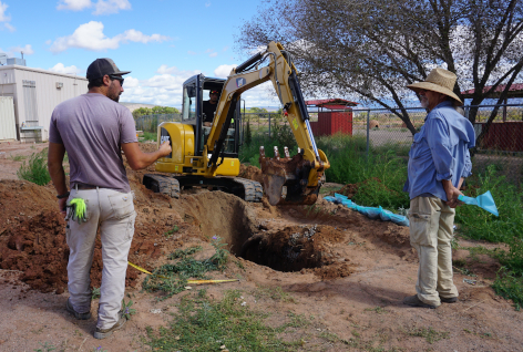 Senior Technician and Designer/Partner evaluate the exposed EZ Flow excavated by CAT track hoe in leachfield of advanced wastewater treatment system at a septic system installation.