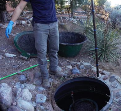 Technician takes sludge measurement of septic tank using dip stick.